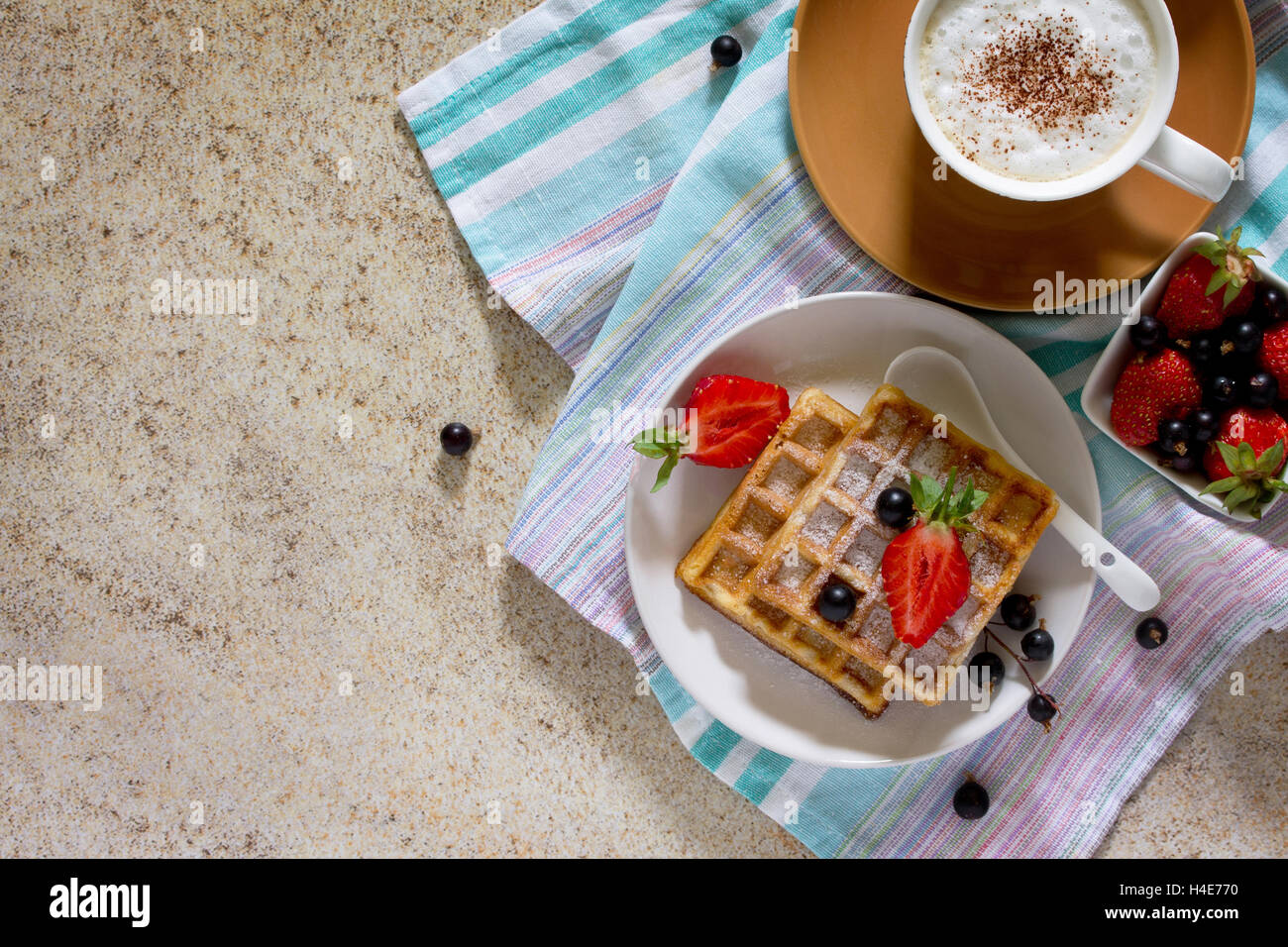 Tradizionale cialde belghe con frutti di bosco freschi sulla pietra sfondo marrone, servito con una tazza di caffè Immagini Stock