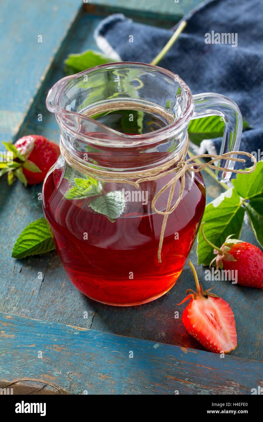 La tradizione estate bere succo di fragole e menta con copia spazio su un annata sullo sfondo di legno. Immagini Stock