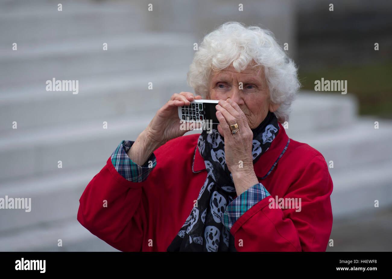 Un anziano pensionato oap utilizzando la tecnologia cellulare per scattare una foto. Immagini Stock