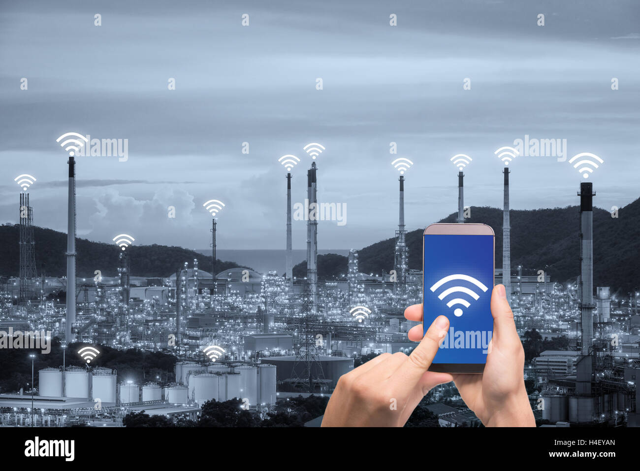 Mano che tiene il controllo dello smartphone rete di comunicazione wireless smart factory e Internet delle cose. Immagini Stock