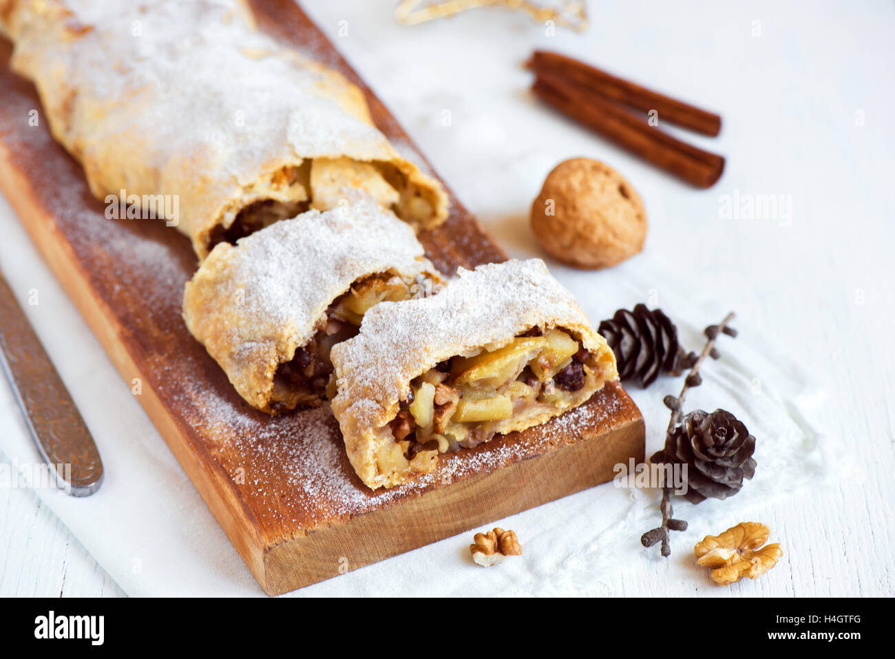 Natale dolci fatti in casa. Strudel di mele (torta) con uvetta, noci e zucchero in polvere con decorazioni di Natale Immagini Stock