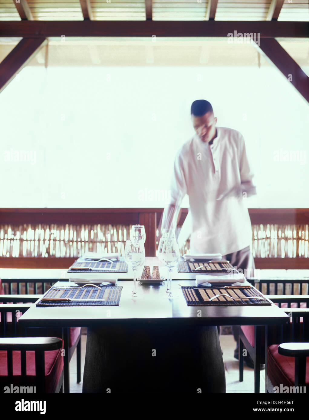 Un cameriere al ristorante di Belem a Le Cap Est Lagoon Resort & Spa imposta un tavolo per il pranzo. Martinica,Carribean. Immagini Stock