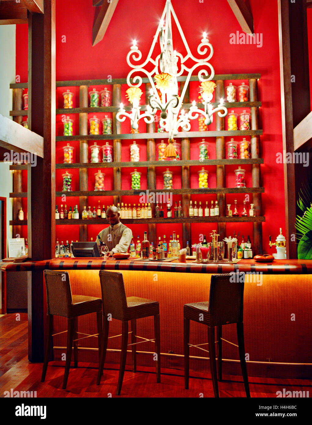 Un barman alla Cohi-bar al Cap Est Lagoon Resort and Spa versa un bicchiere di vino rosso. Le François, Martinica. Immagini Stock