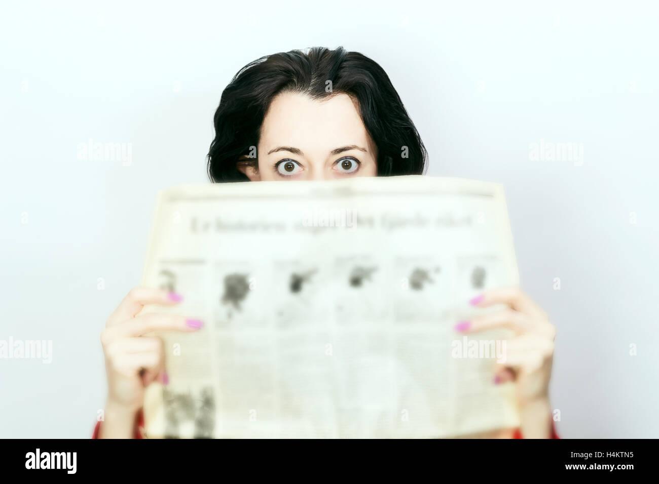 Bellezza Donna bruna con quotidiano in stato di shock Immagini Stock