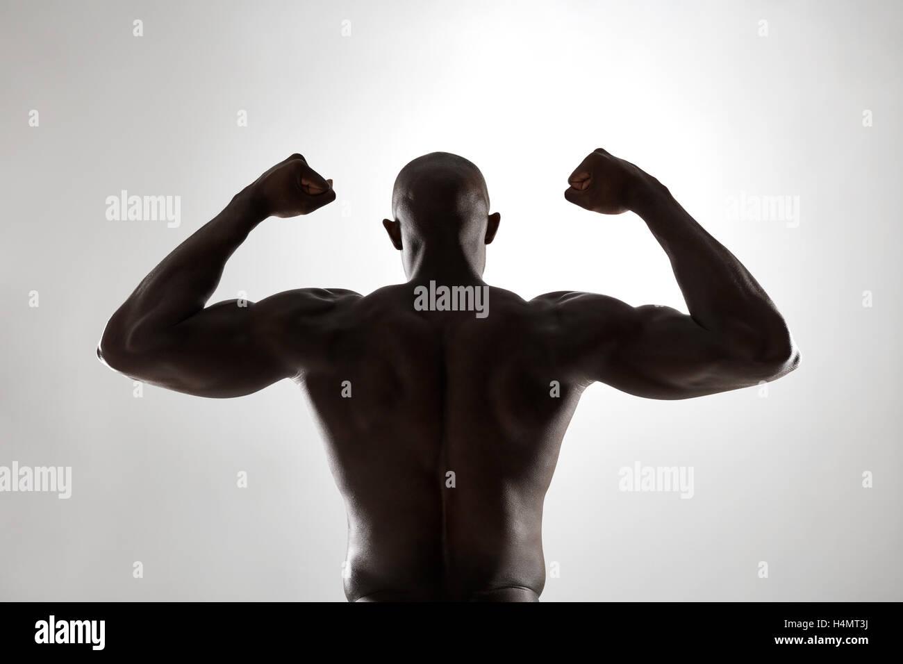 Schiena forte di un nero uomo muscolare flettendo le braccia contro uno sfondo grigio. Vista posteriore del fitness Immagini Stock
