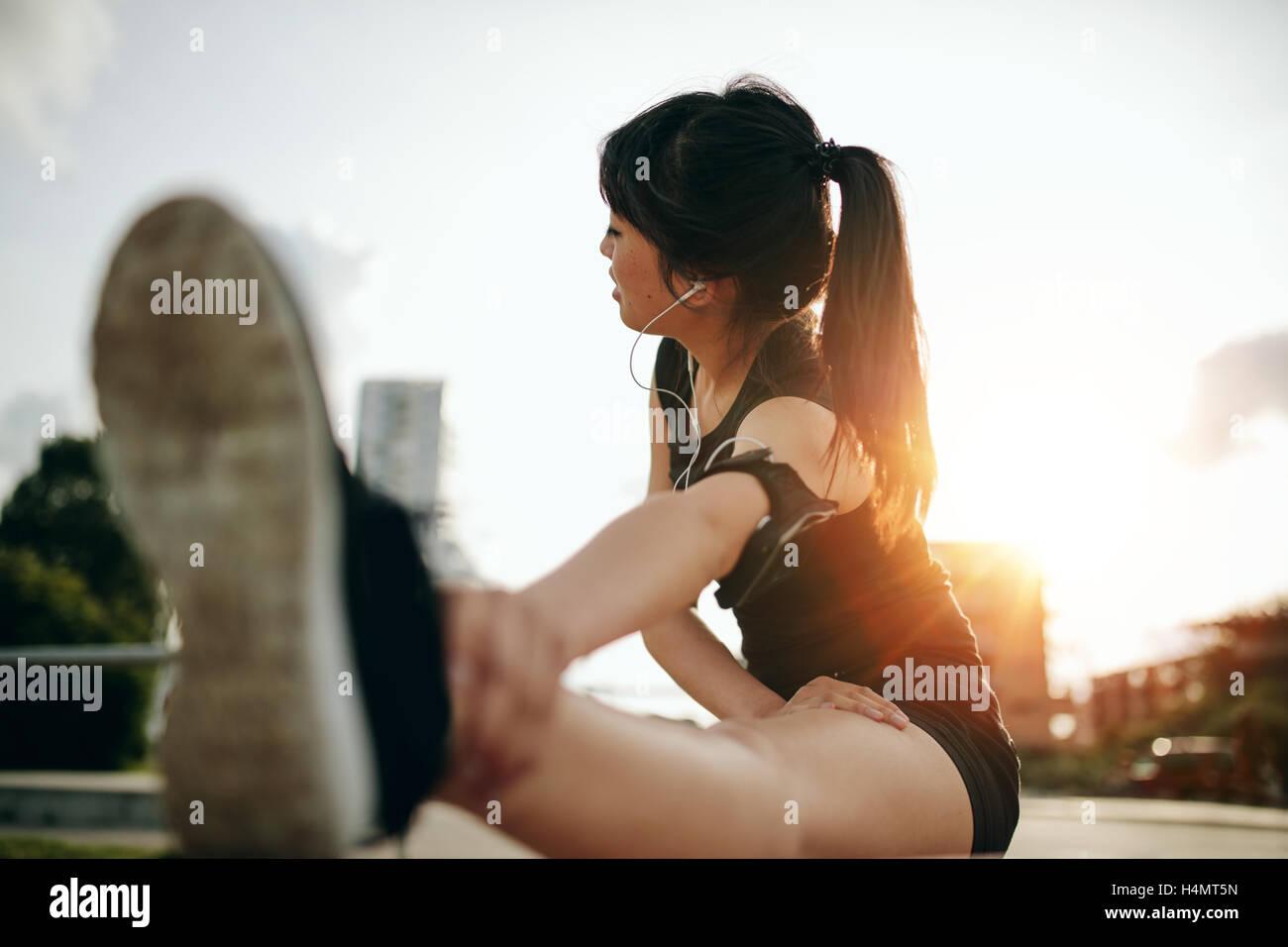 Colpo di giovane donna stretching le gambe dopo una corsa in città. Femminile di esercitare nella mattina. Immagini Stock