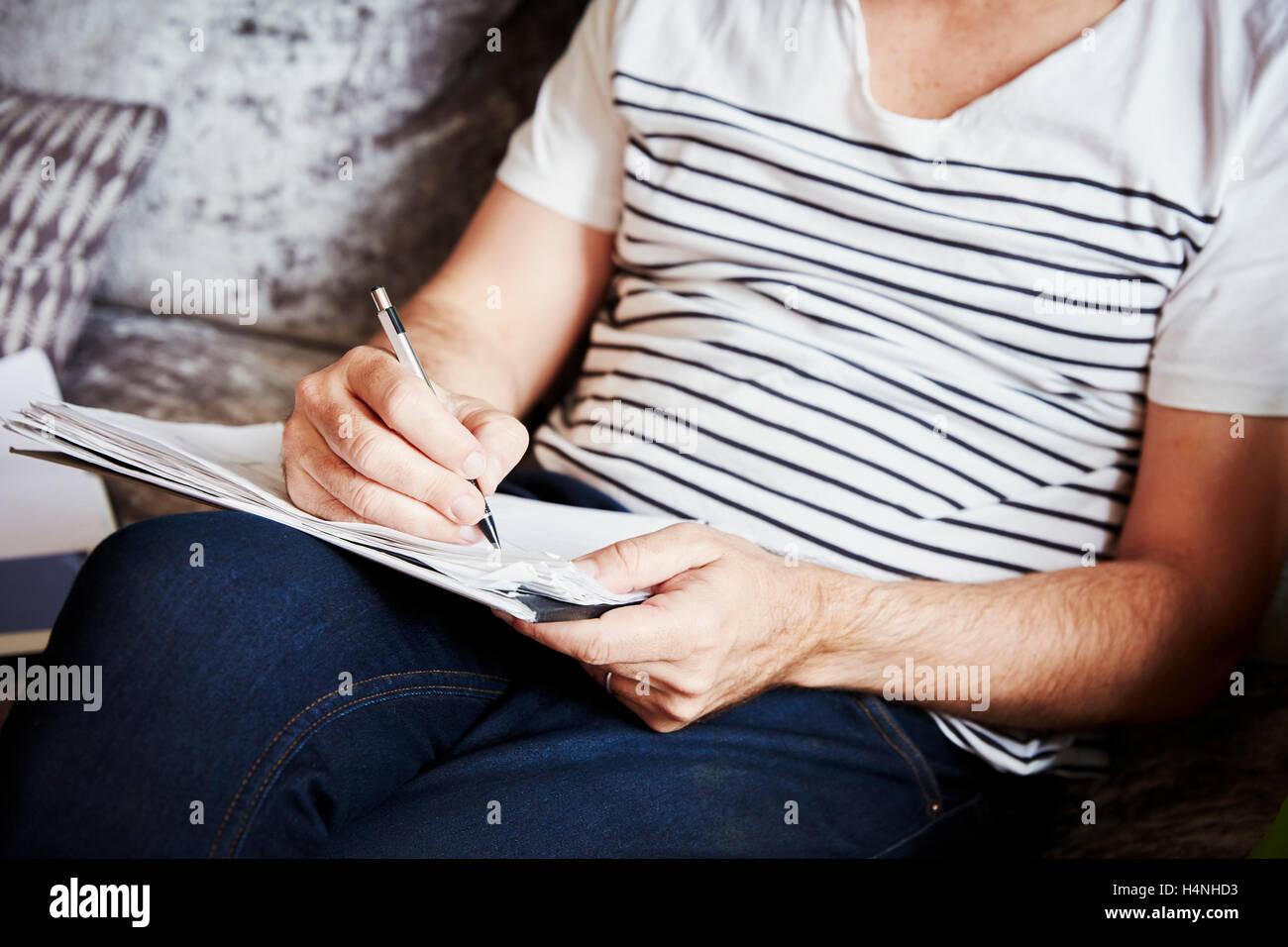Un uomo seduto utilizzando una penna e schizzi di disegno, un progettista al lavoro. Foto Stock