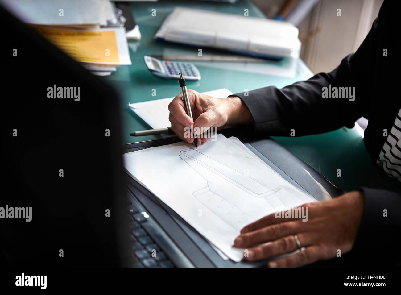 Un uomo seduto alla scrivania in ufficio, disegnare, progettare e schizzi. Foto Stock