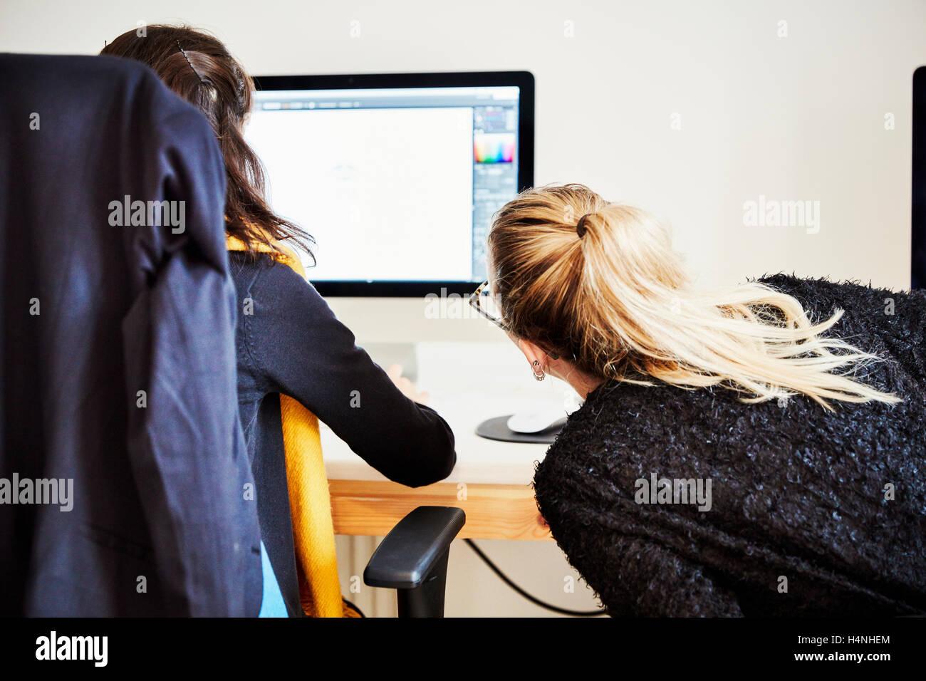 Due donne seduti condividere lo schermo di un computer e di discutere il contenuto grafico. Immagini Stock