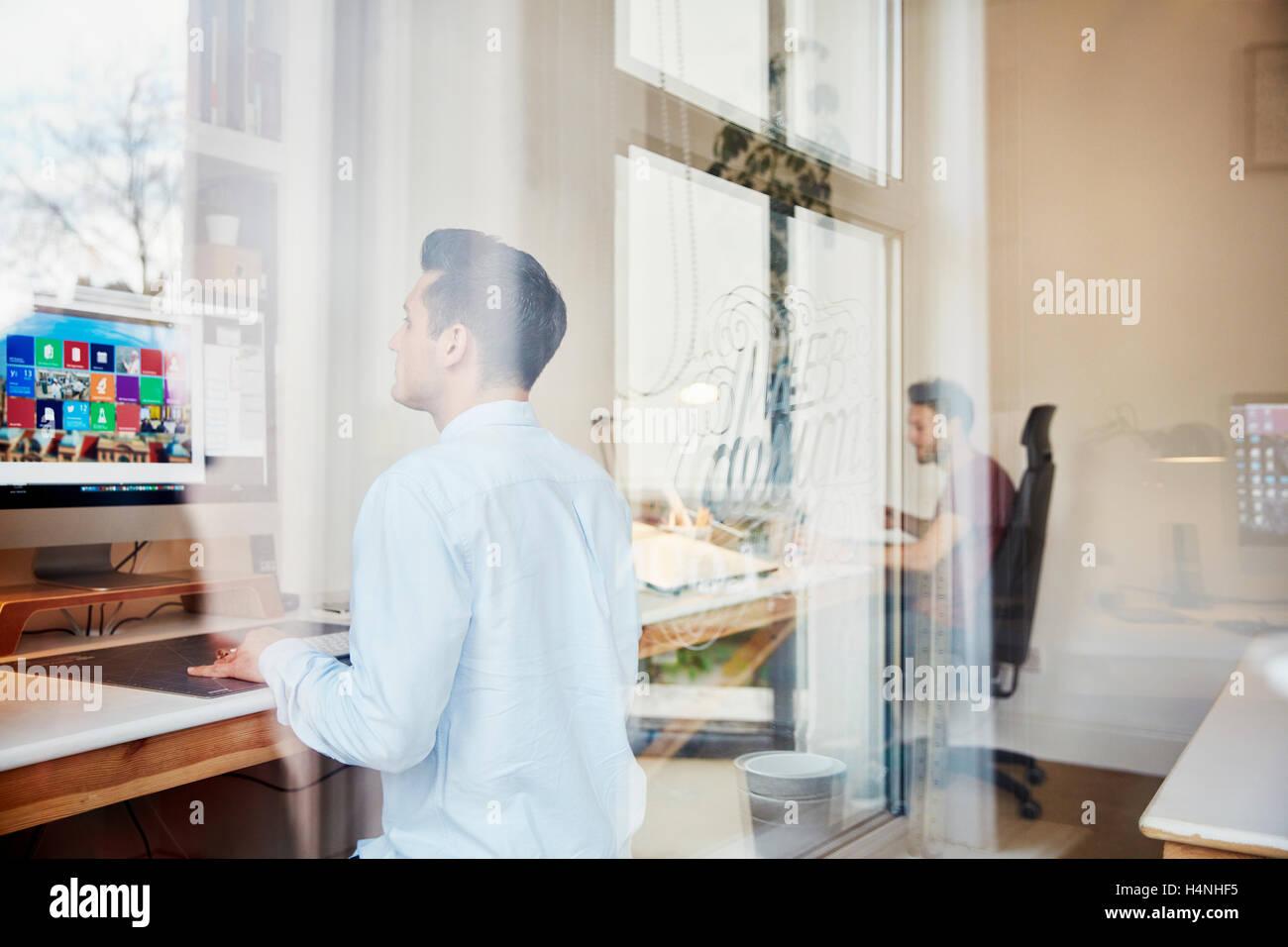 Due uomini al lavoro sul computer in uno studio di design for Piano del telaio della finestra