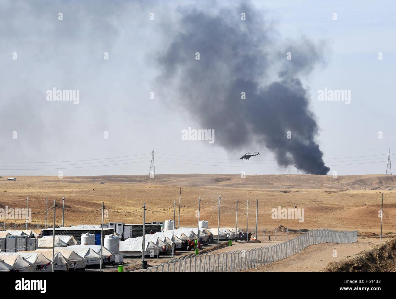 Un elicottero e fumo nero da un brucia olio impianto può essere visto dietro il Debaga Refugee Camp tra Mosul e Foto Stock