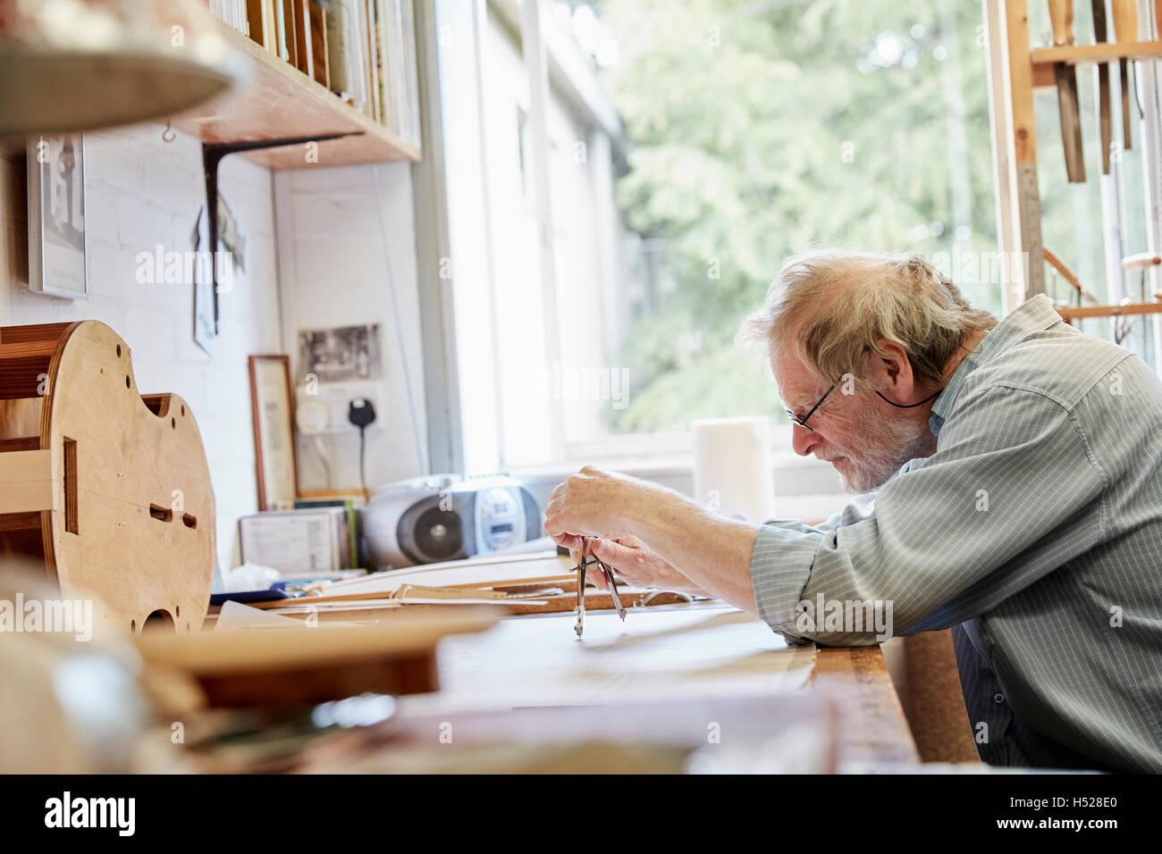 Un liutaio presso il suo tavolo da disegno disegno fuori i piani e la bozza di un nuovo strumento. Immagini Stock