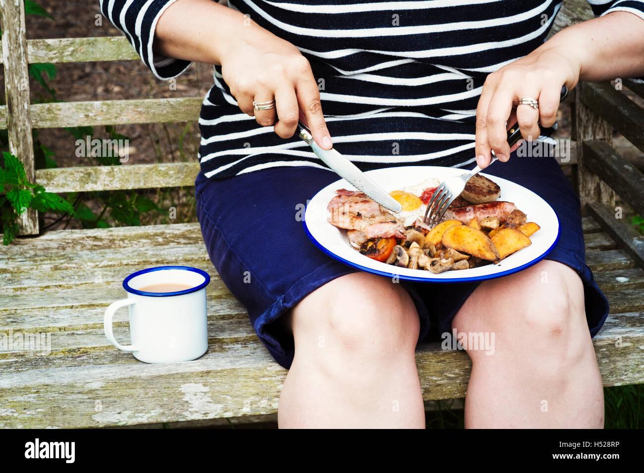 Donna seduta su una panchina di mangiare da un piatto di cibo bilanciato sulle sue ginocchia. Immagini Stock