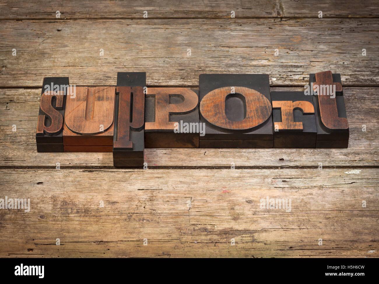 Supporto, parola scritta con l'annata tipografia su blocchi di legno rustico sfondo Immagini Stock