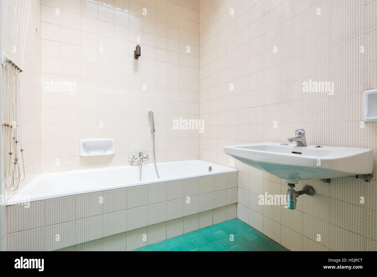 Antico bagno interno rivestito di piastrelle con vasca da bagno