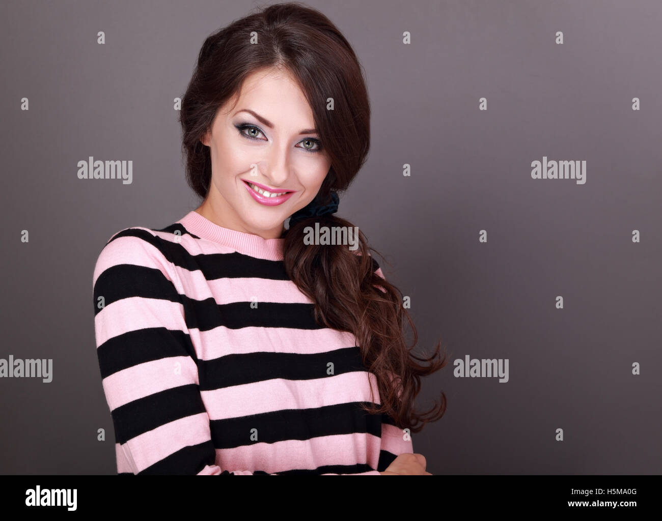 Felice bella donna informale con lunghi capelli ricci style guardando con  sorriso su sfondo grigio Immagini c9bb84ef8550