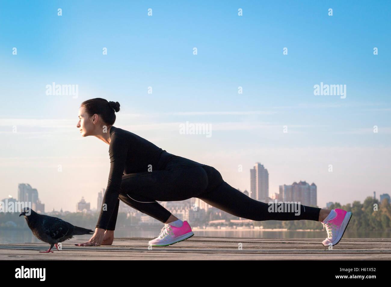 Giovane bella donna fitness esercita sul molo durante la mattina sport training allenamento Immagini Stock