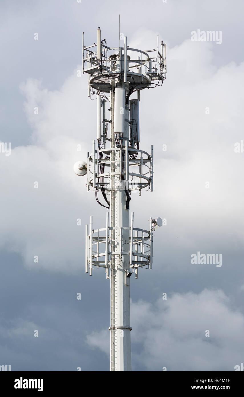 Le comunicazioni e la torre cellulare montante. Immagini Stock