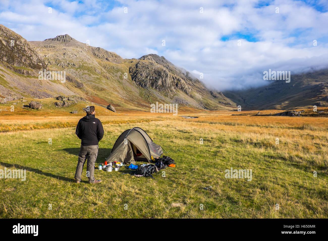 Campeggio selvaggio nella parte superiore della valle Esk nel distretto del lago, un giovane uomo si distingue per Immagini Stock