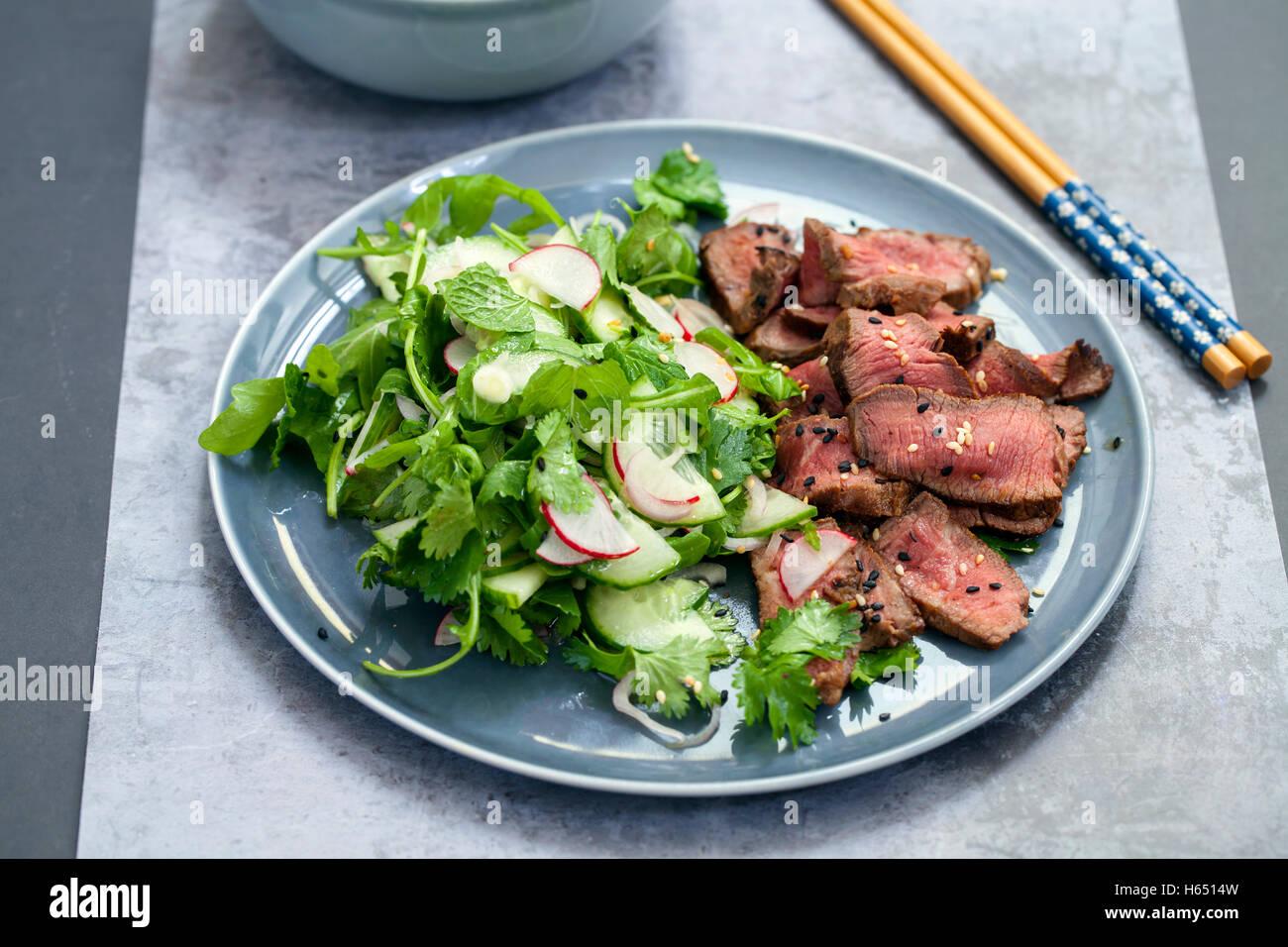 Carni bovine asiatici con insalata di cetrioli e insalata di erbe e in bianco e nero di semi di sesamo Immagini Stock