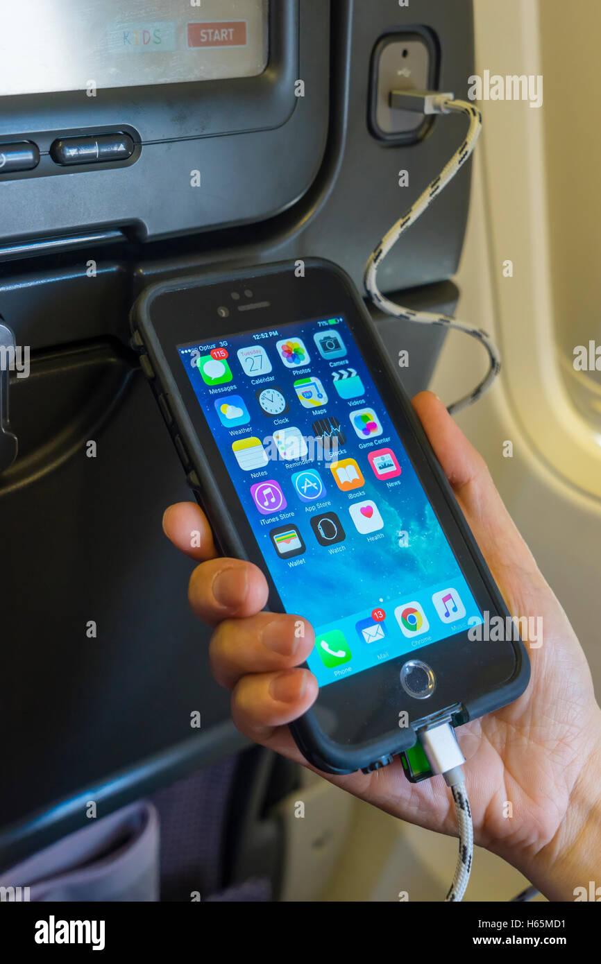 La ricarica il telefono cellulare a bordo di un aeromobile Immagini Stock
