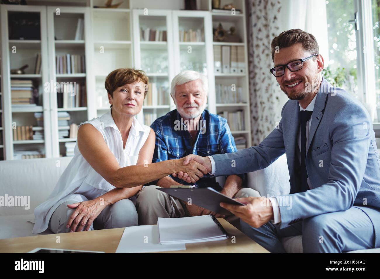 Advisor finanziario stringono le mani con i senior donna Immagini Stock
