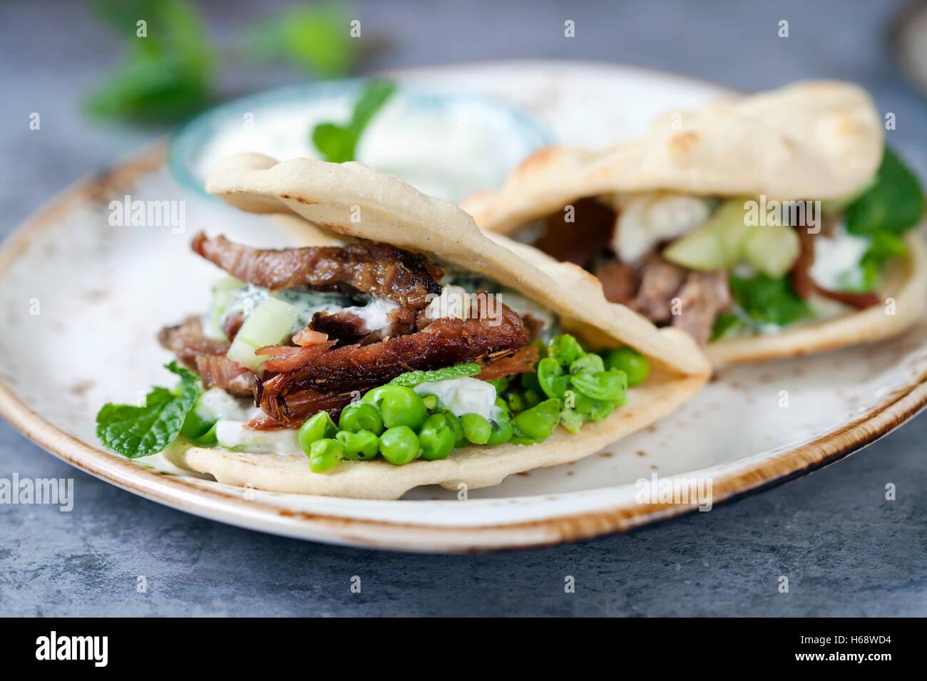 Mini piatto con pane croccante di agnello, purea di piselli, cetriolo, menta e salsa di yogurt Immagini Stock
