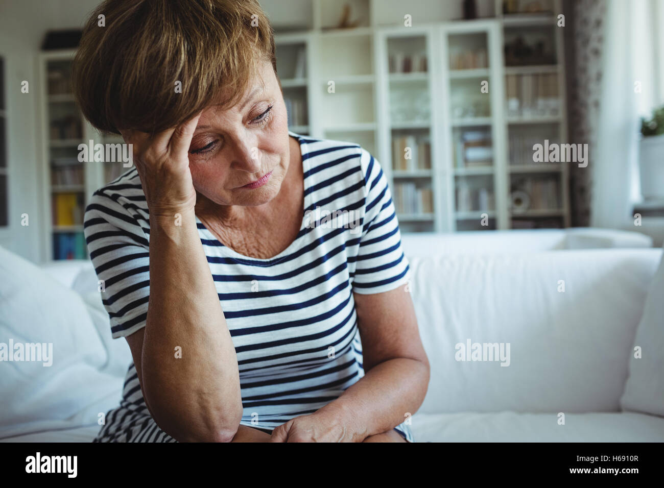 Tense donna seduta sul divano nel soggiorno Immagini Stock