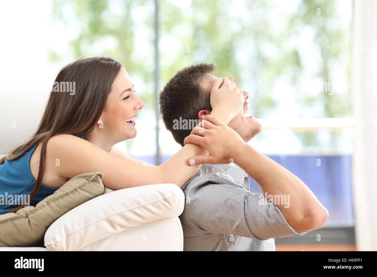 Giocoso giovane che copre gli occhi a casa con una finestra in background Immagini Stock