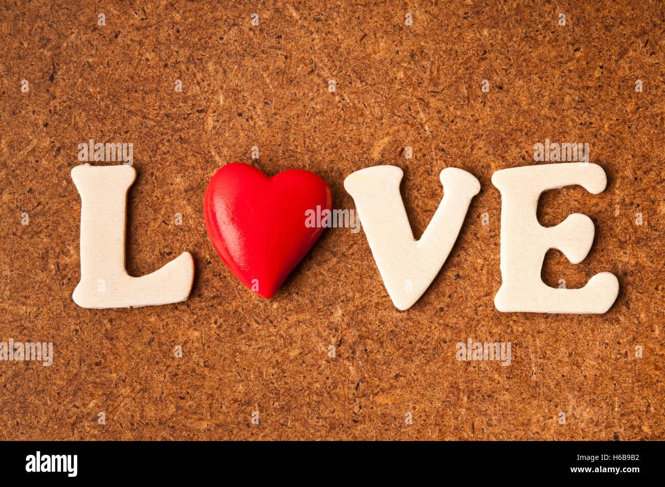 La parola amore formata con lettere in legno e una a forma di cuore ad coriandoli, concetto di amore Immagini Stock
