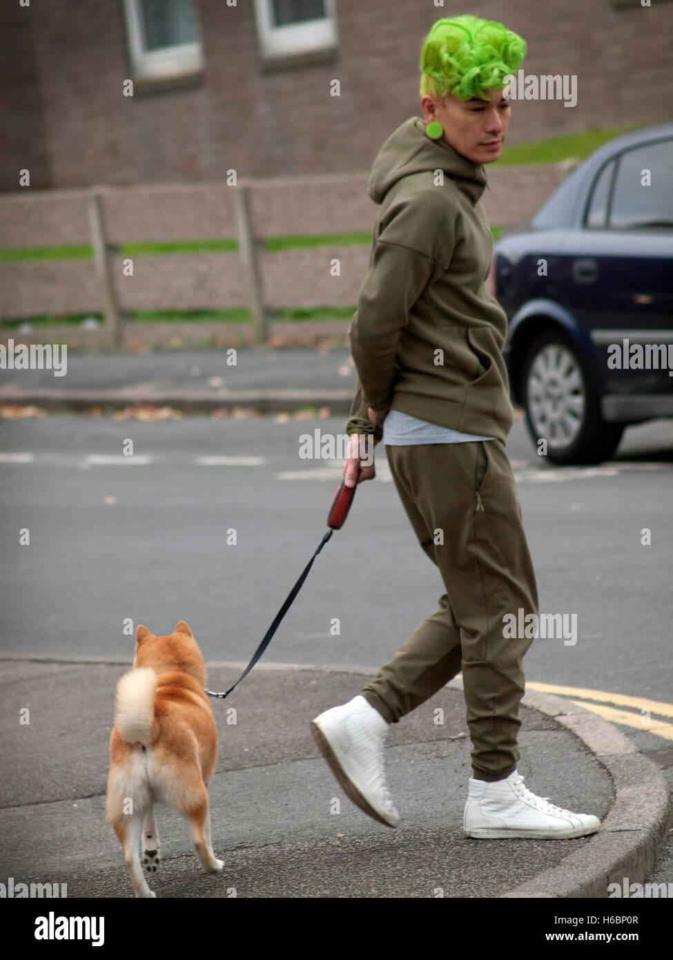 In Brighton un uomo con i capelli verdi prende il suo cane per una passeggiata Foto Stock