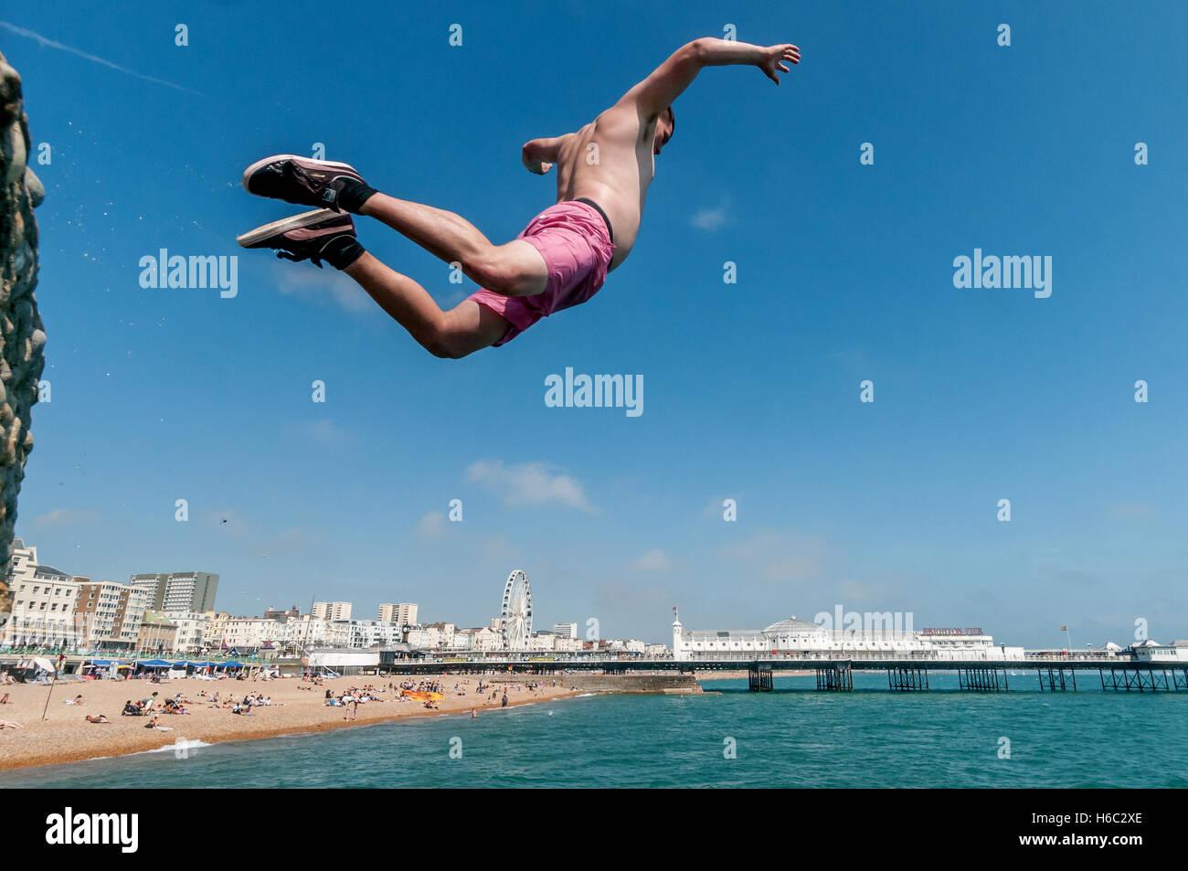 Ragazzo le immersioni in mare sulla spiaggia di Brighton Immagini Stock