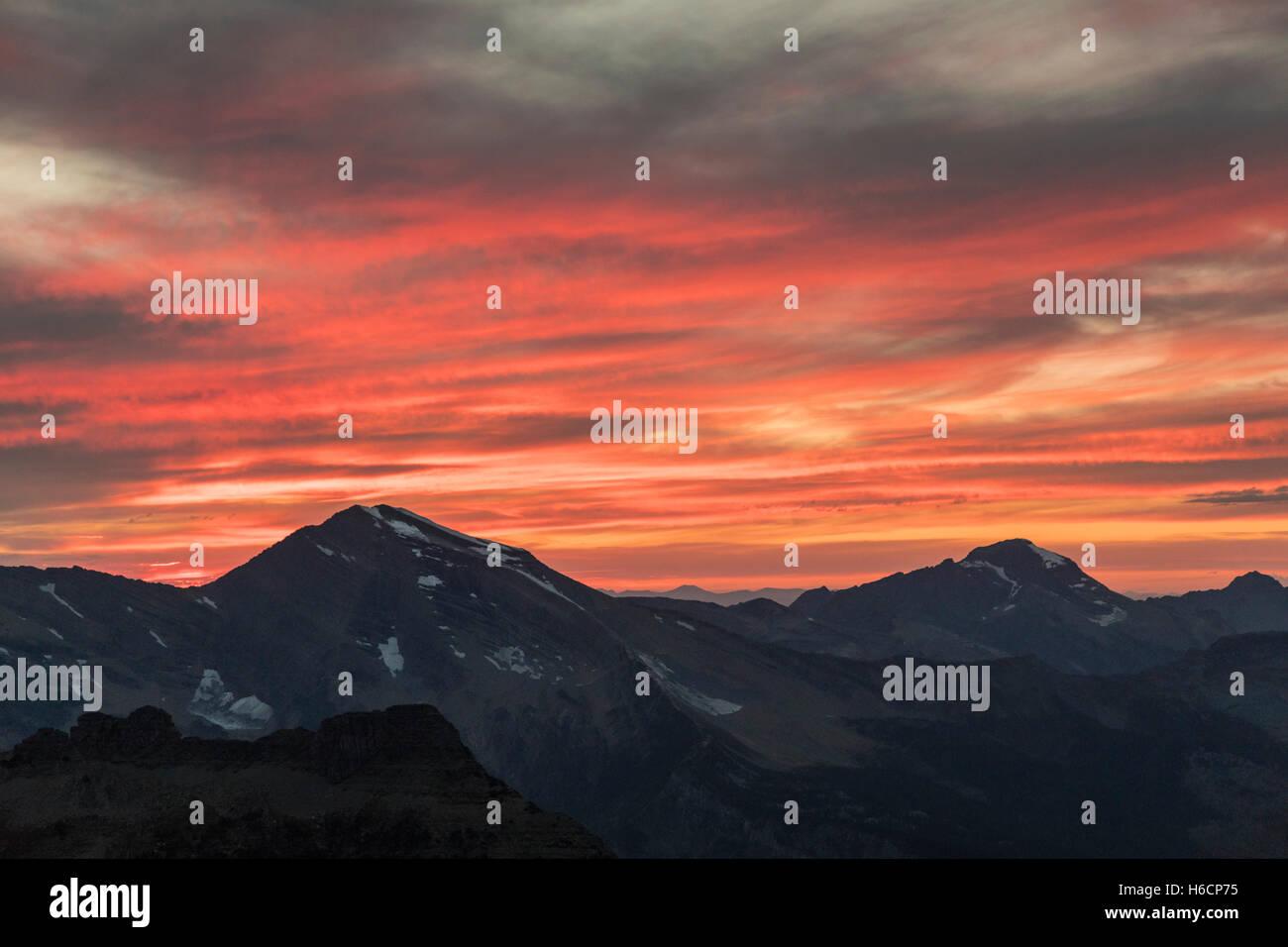 Un tramonto alpino imposta al di sopra dei cieli picco nella gamma Livingston presso il Glacier National Park Settembre Immagini Stock