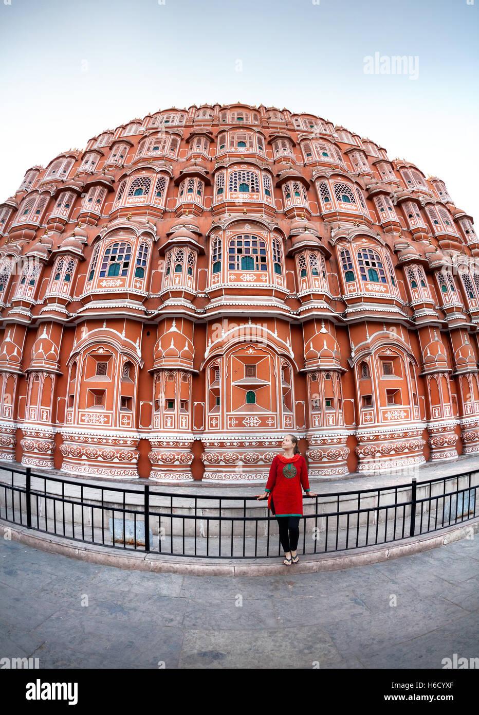 Donna in abito rosso con sciarpa in piedi vicino alla facciata del Hawa Mahal, Rajasthan, India Immagini Stock