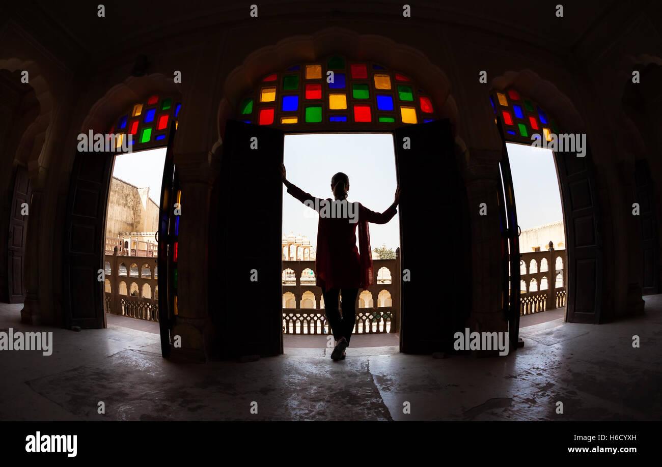 Donna con sciarpa in silhouette in piedi in arco con mosaico di vetro di Hawa Mahal, Rajasthan, India Immagini Stock