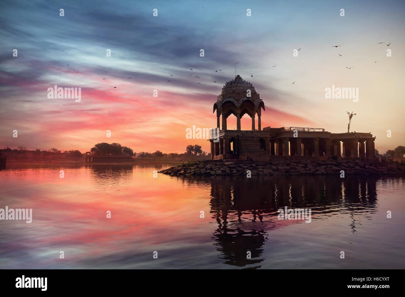 Silhouette di un tempio sulla Gadi Sagar lago a rosa vibrante Cielo di tramonto in Jaisalmer, Rajasthan, India Immagini Stock