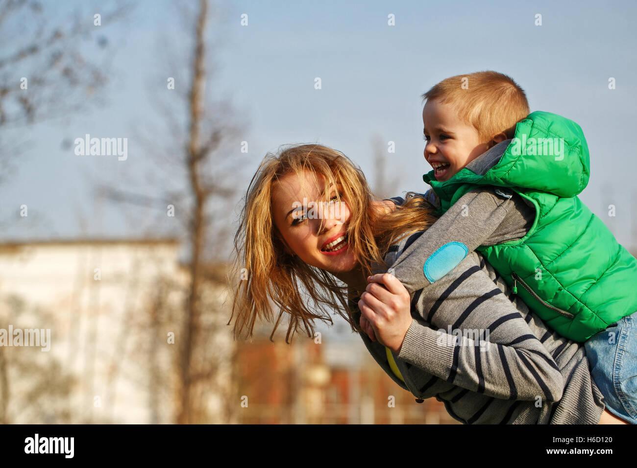 Mom rotoli suo figlio sulle sue spalle in autunno park. Tempo per la famiglia. La felicità di infanzia e genitorialità. Immagini Stock