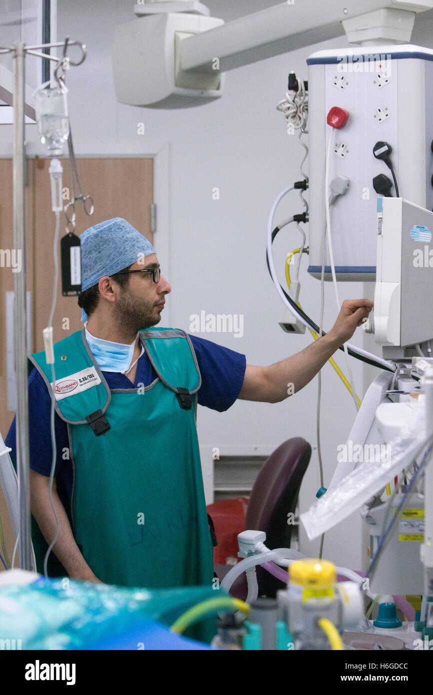 Un anestesista controlla un gocciolamento medica durante un funzionamento in un teatro ospedaliero Immagini Stock