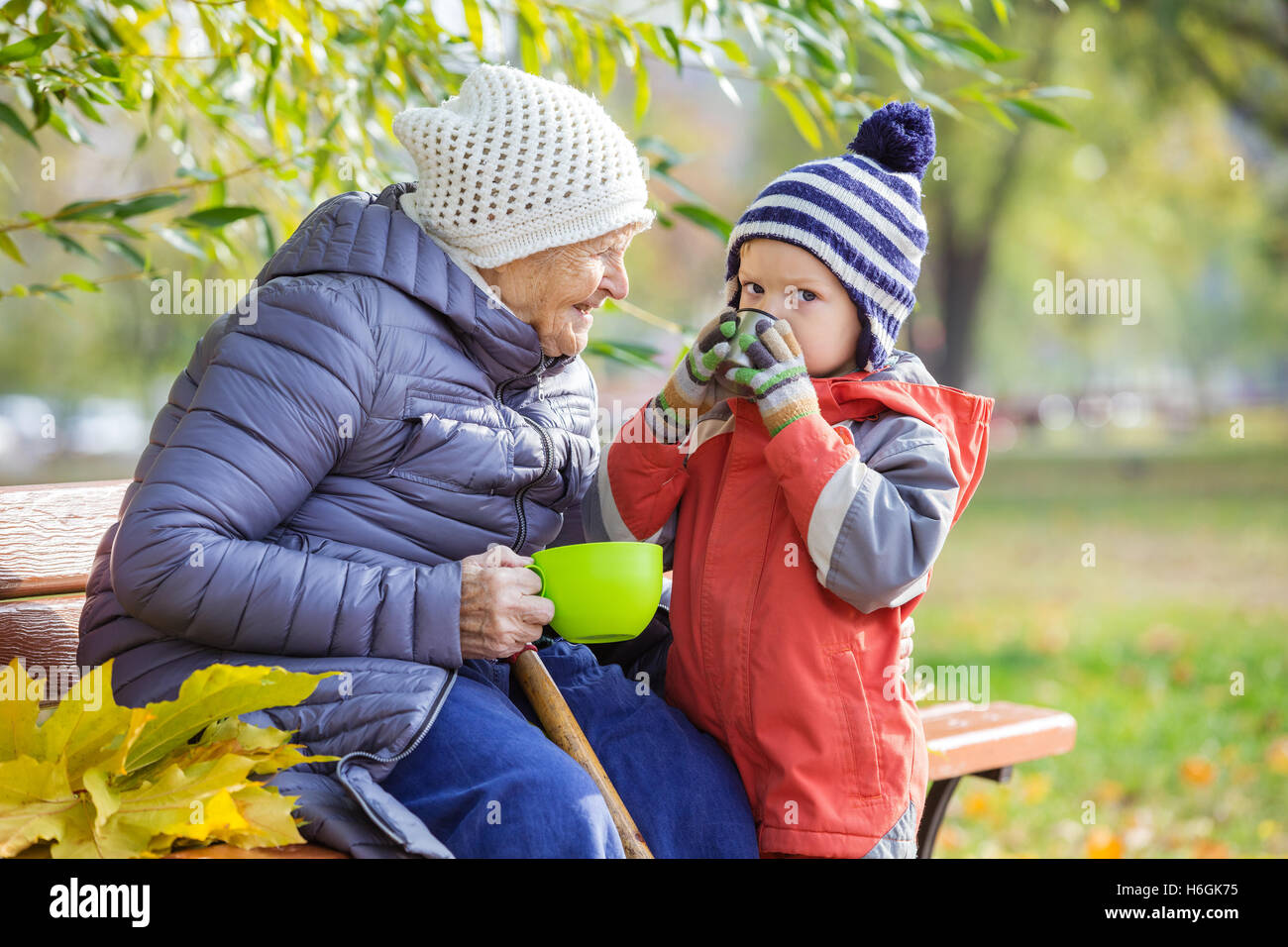 Senior la donna e la sua pronipote di bere il tè caldo in autunno park Foto Stock