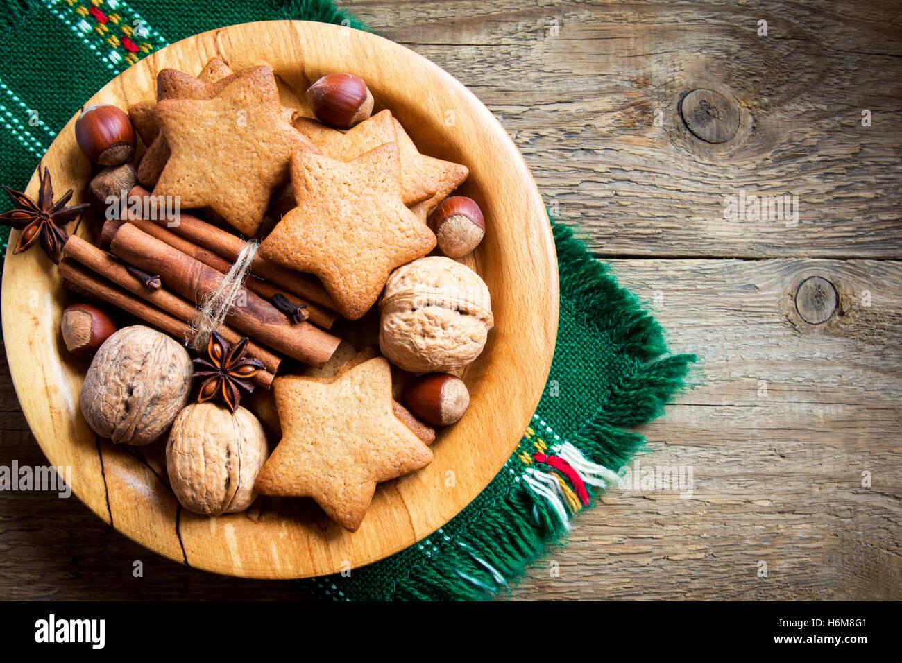 Rustico decorazione di Natale con pan di zenzero i cookie, i dadi e le spezie di Natale su sfondo di legno con spazio Immagini Stock