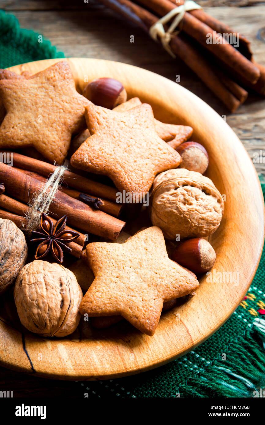 Rustico decorazione di Natale con pan di zenzero i cookie, i dadi e le spezie di Natale sul piatto di legno vicino Immagini Stock