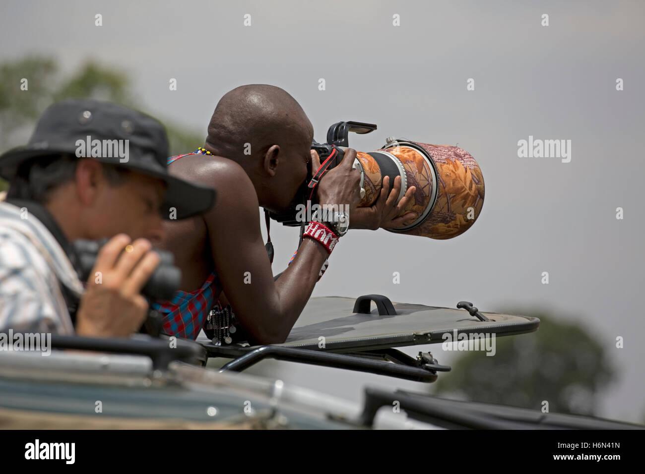 African Masai driver guida utilizzando lungo un teleobiettivo Masai Mara Kenya Immagini Stock