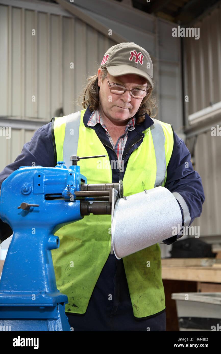 Un lavoratore rotoli di un nastro metallico in una officina di fabbricazione su misura la costruzione di sezioni Immagini Stock