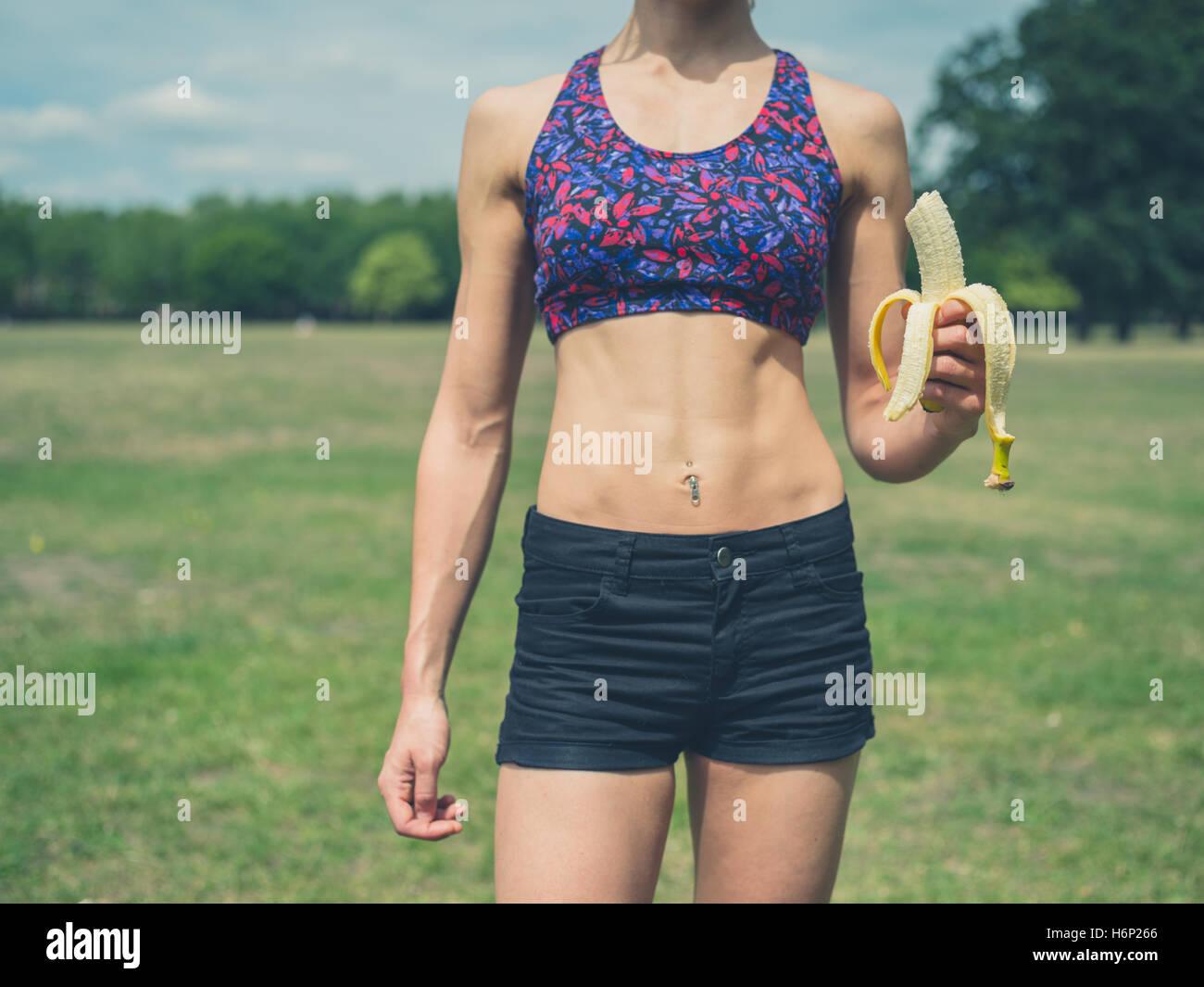 A montare e atletica giovane donna è in piedi in un parco con una banana Immagini Stock