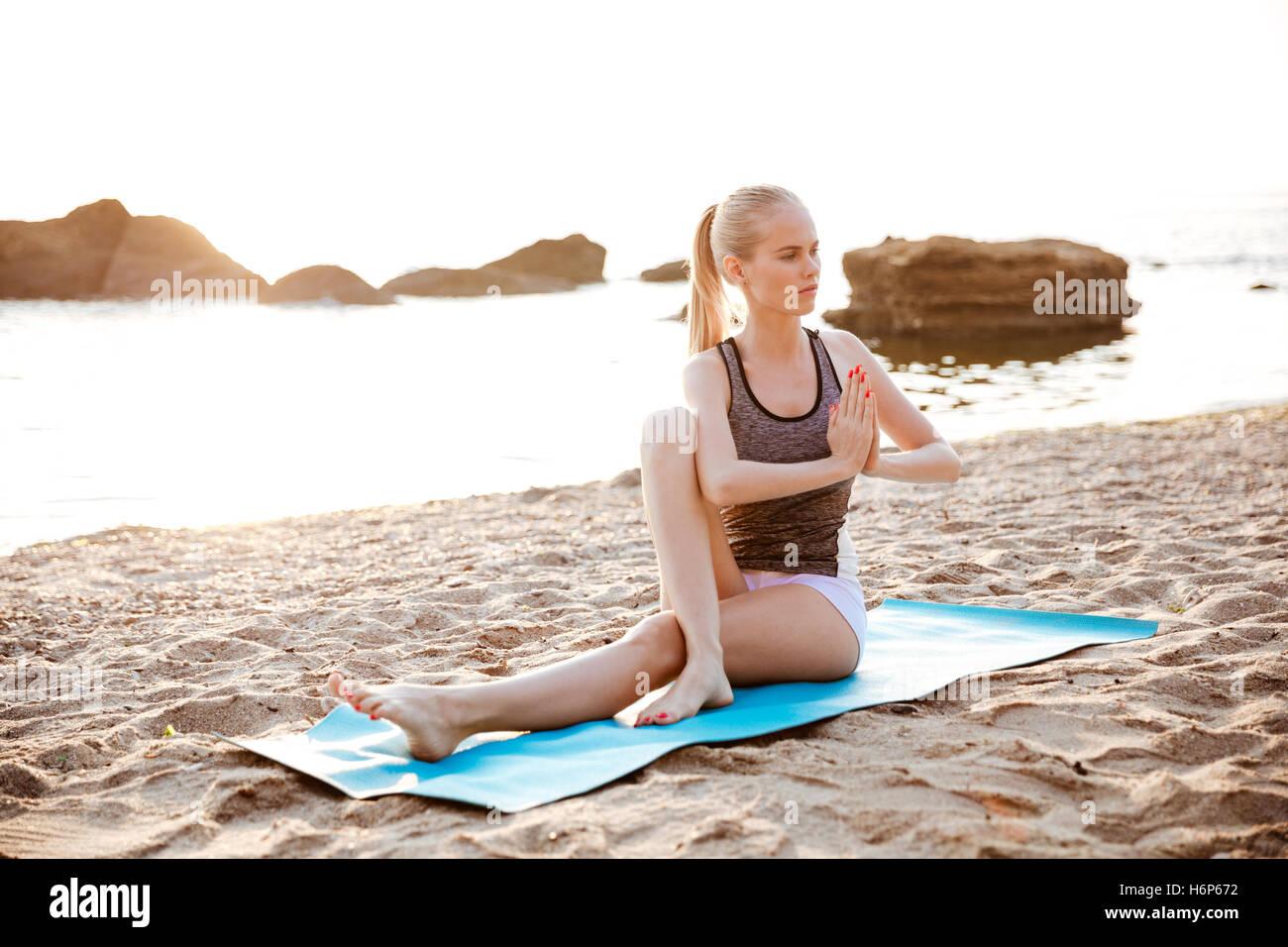 Ritratto di una giovane ragazza facendo esercizi di stretching sulla spiaggia di mattina Immagini Stock