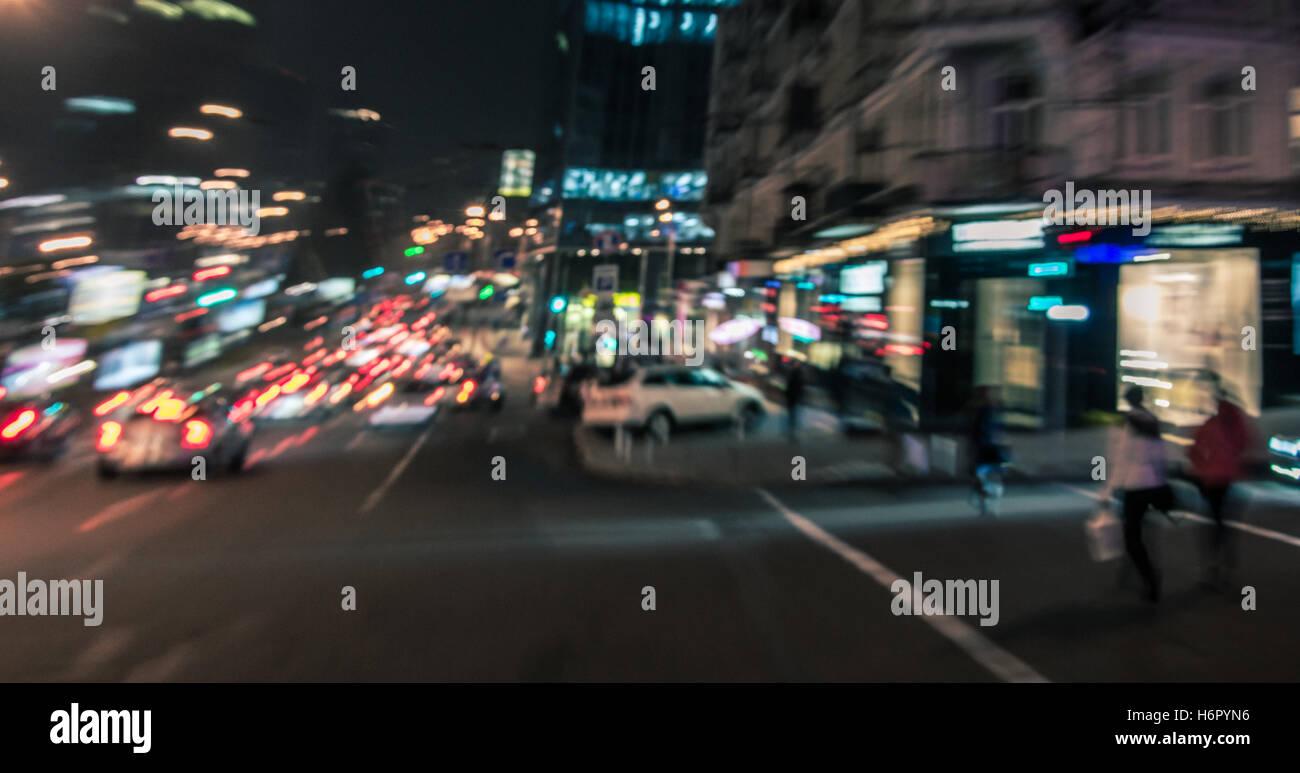 La città di notte le luci di strada dello sfondo. Sfocato il movimento di persone e di automobili Immagini Stock
