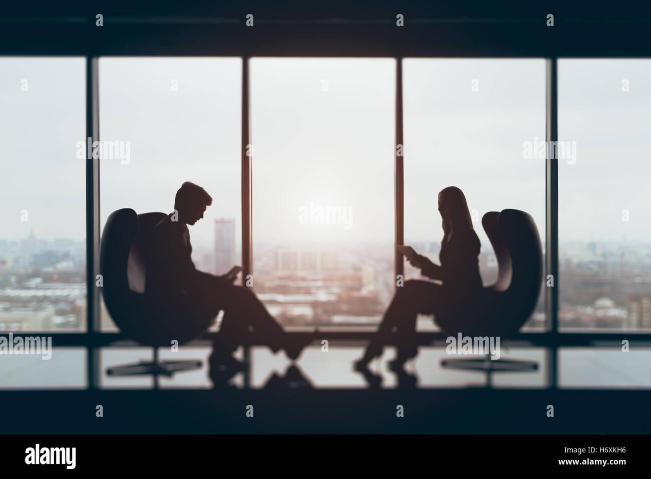 Vero tilt shift riprese di imprenditore e imprenditrice seduti di fronte a vicenda con i loro gadget in office Immagini Stock