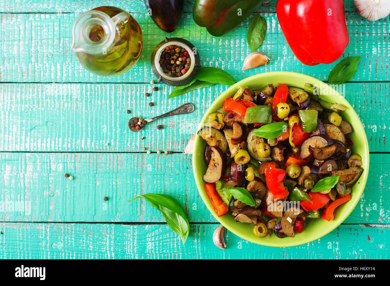 Piccante stufato di melanzane, peperoni, olive e capperi con le foglie di basilico. Vista superiore Immagini Stock