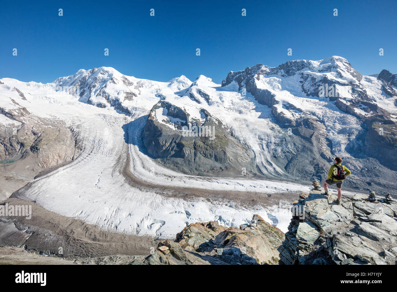 Escursionista guardando oltre il Gorner Glacier e il Monte Rosa dal Gornergrat. Zermatt, Pennine, Vallese, Svizzera. Immagini Stock