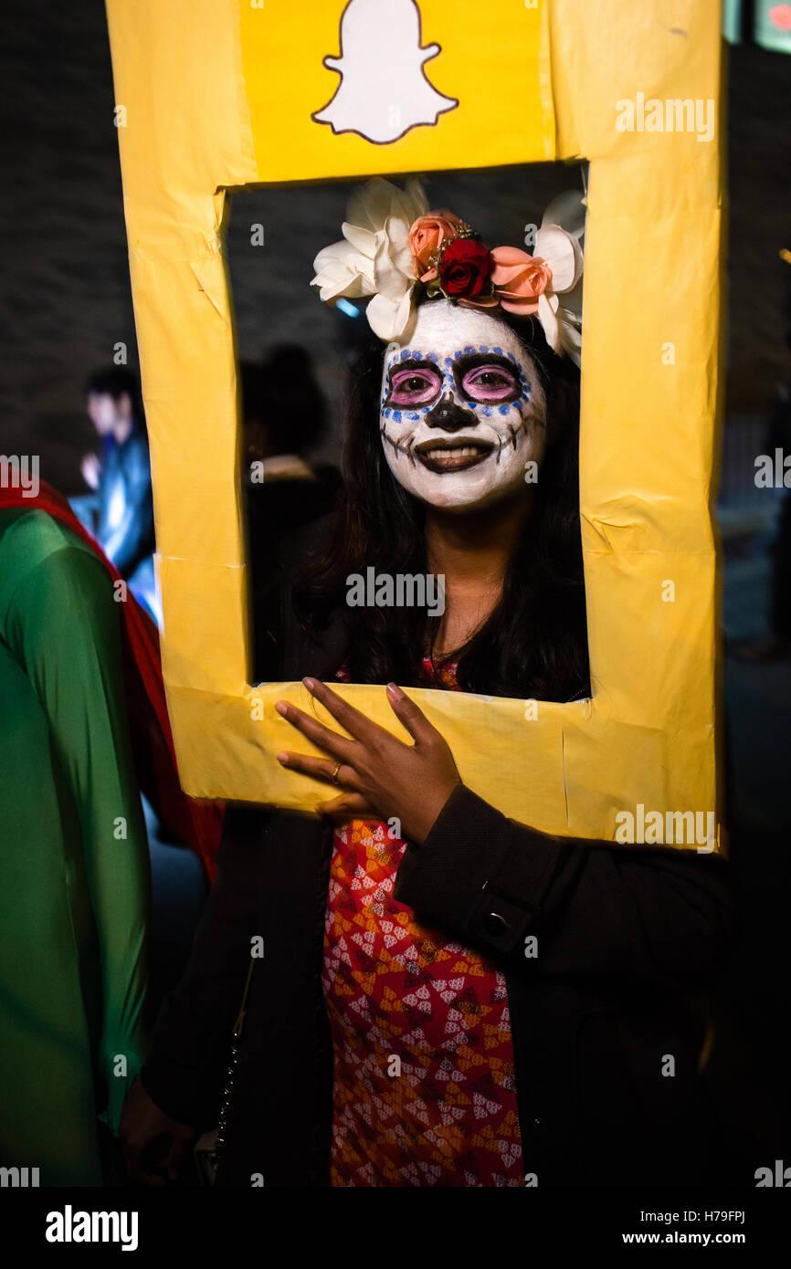 New York, NY - 31 ottobre 2016. Una donna con la faccia dipinta come la Calavera Catrina dietro un telaio Snapchat nella Villa di Greenwich Foto Stock